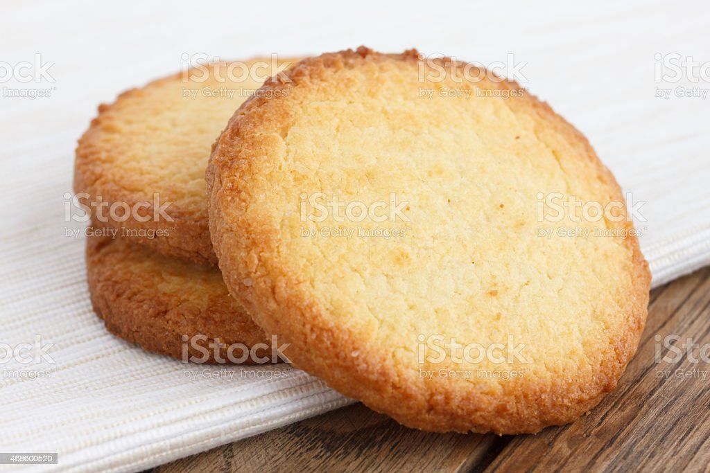 Three butter biscuits on napkin and wood. stock photo