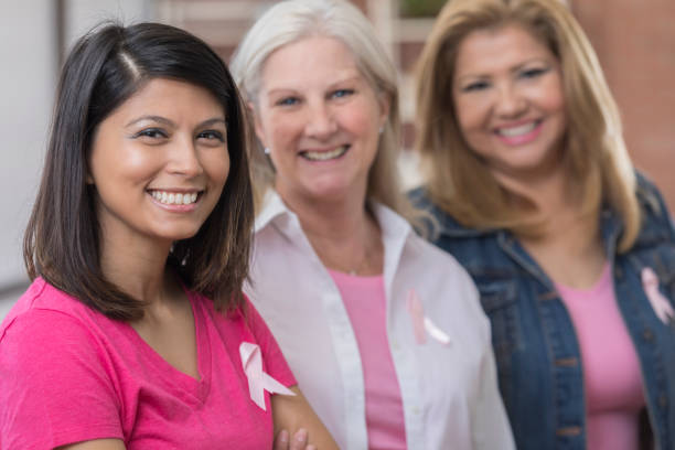 Three cancer survivors stand side by side and smile stock photo