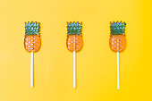 Three candies in the form of pineapple on a yellow background. Pattern flat lay
