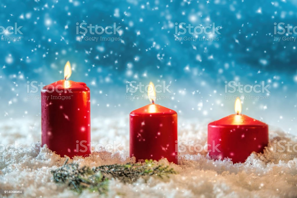 Three candles in the snow greetings card stock photo