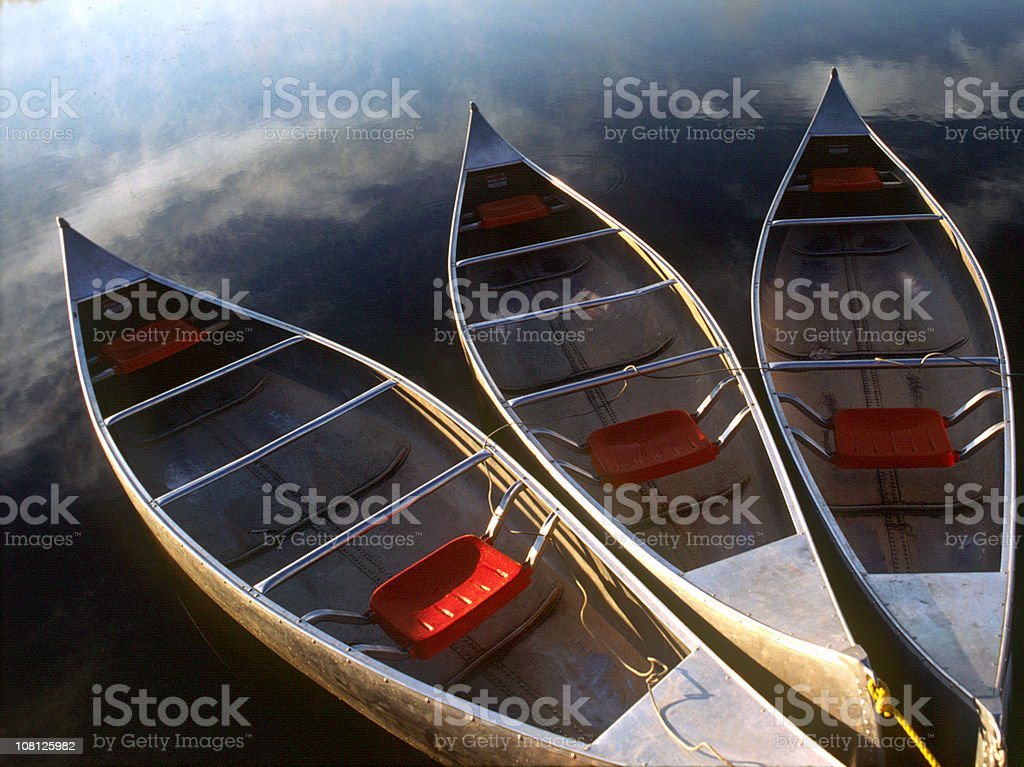 Three Canoes Floating in Calm Water stock photo