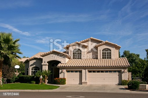 Two story home with three car garage in southwestern neighborhood of Scottsdale, AZ has tiled roof, palm trees, is new,