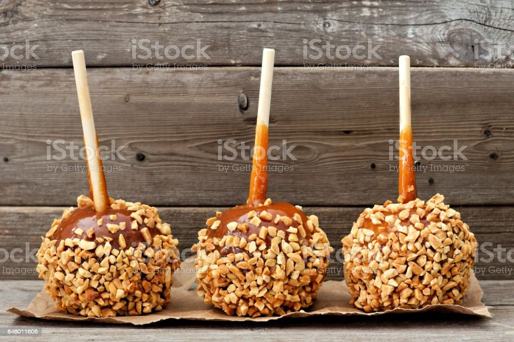 Three caramel apples with nuts against rustic wood stock photo