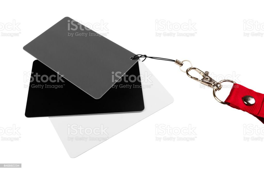 Three cards, one white, one grey and one black, attached together, and on a red strap, on a white surface. isolated on white background stock photo