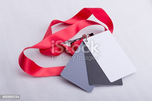 istock Three cards, white, grey and black, on a red strap. 835893234