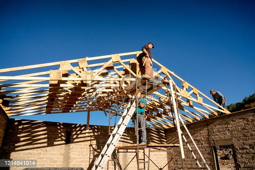 Three Men finishing up on the trusses so the sheeting can go on a new church building in a remote village of Mexico