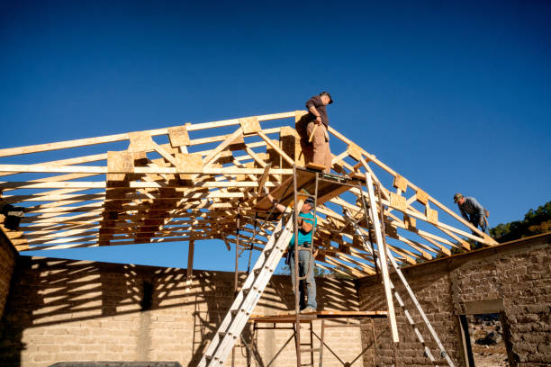 Three Carpenters Setting Trusses On A New Church Building stock photo