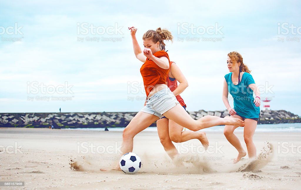 Three casual female friends playing beach soccer together stock photo