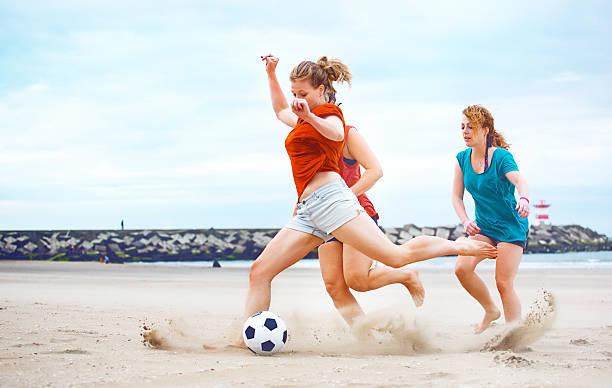 three casual female friends playing beach soccer together - futebol de areia - fotografias e filmes do acervo