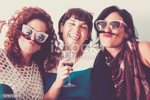 three caucasian females friends stay together in friendship and craziness using hair like moustache and happiness relationship concept. vintage full colors and enjoyment leisure activity. summer time.