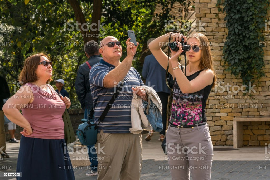 Three caucasian tourist wearing sunglasses at a public square in Budapest taking pictures. stock photo