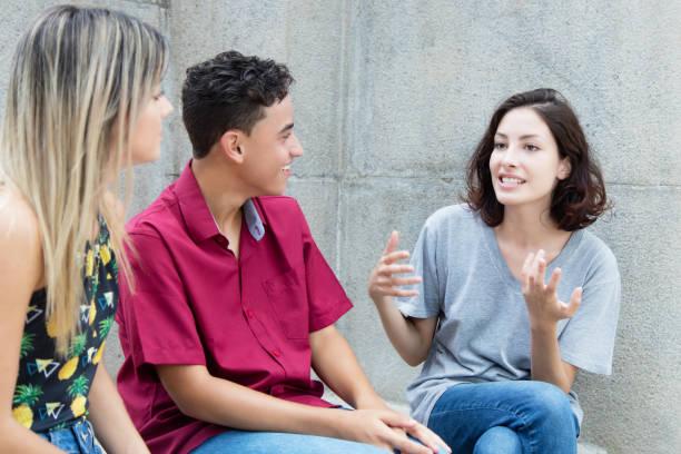 drei kaukasischen junge erwachsene in diskussion - deutsche frauen stock-fotos und bilder