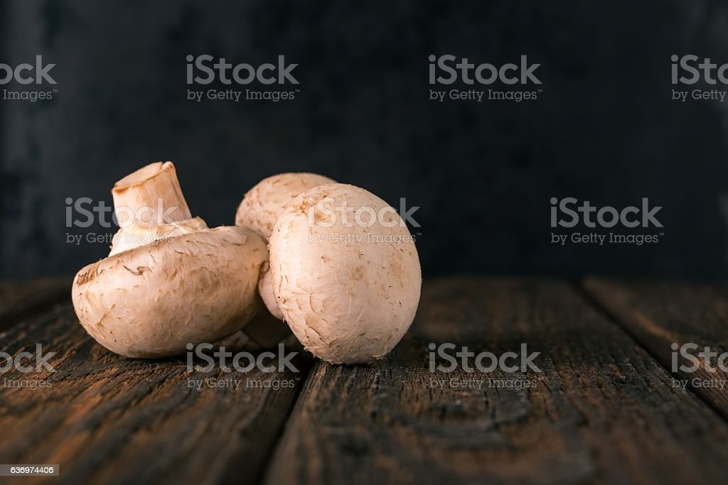 Three champignon mushrooms on dark wooden board stock photo