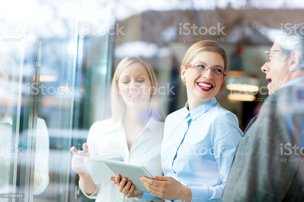 Three cheerful  businesspeople looking on a touchpad stock photo