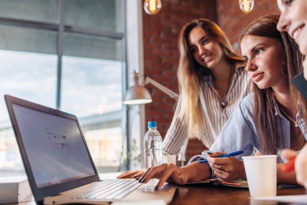 drie vrolijke vrouwelijke studenten surfen op het internet met behulp van laptop samen zoeken naar de informatie - e learning stockfoto's en -beelden