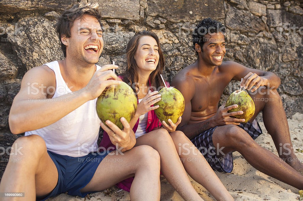Three cheerful friends enjoying coconut drinks on beach. royalty-free stock photo