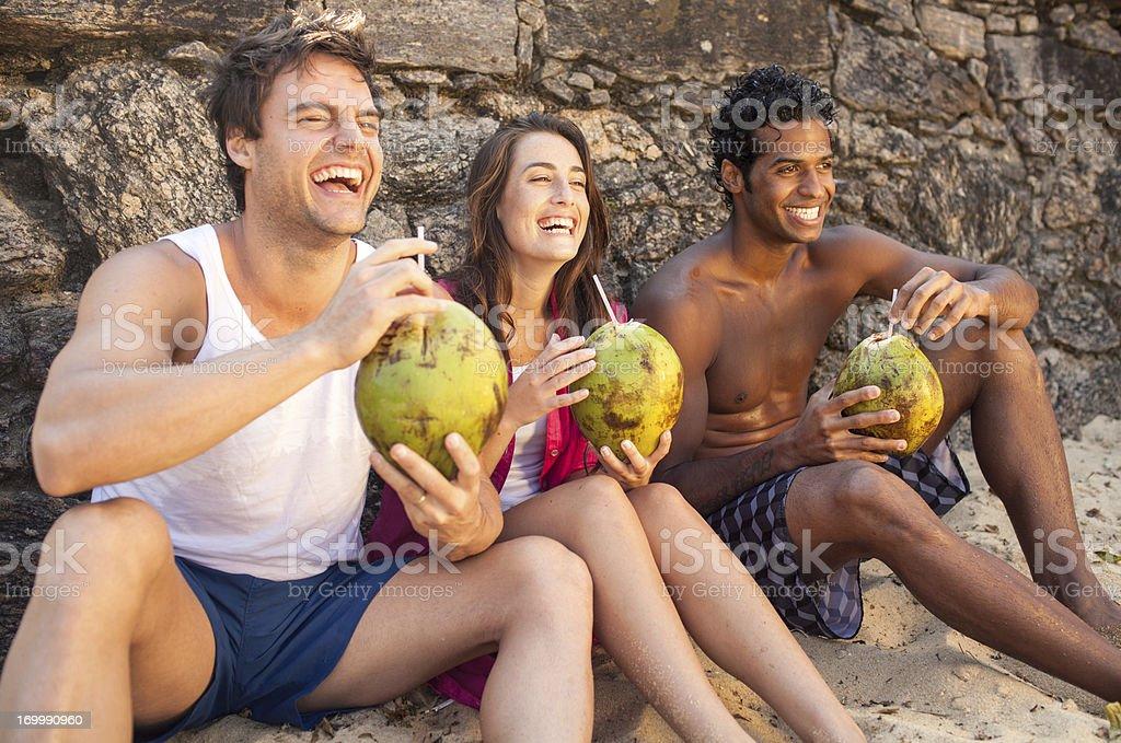 Three cheerful friends enjoying coconut drinks on beach. stock photo