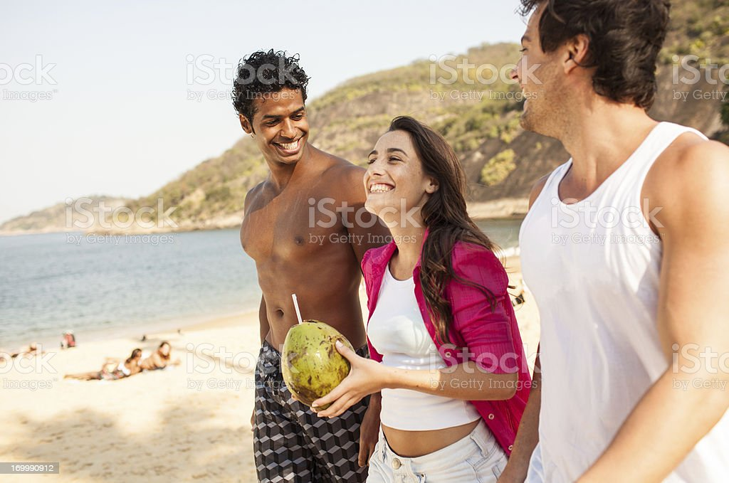Three cheerful friends have fun on the beach. stock photo