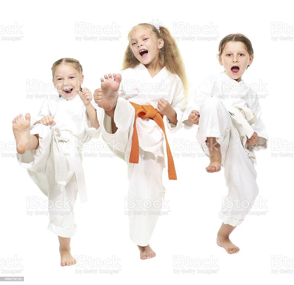 Three cheerful girl dressed in a white kimono kick leg stock photo