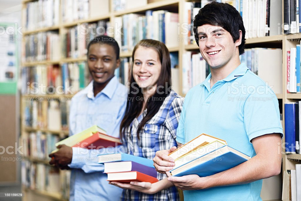 Three cheerful students standing with books among library shelves royalty-free stock photo