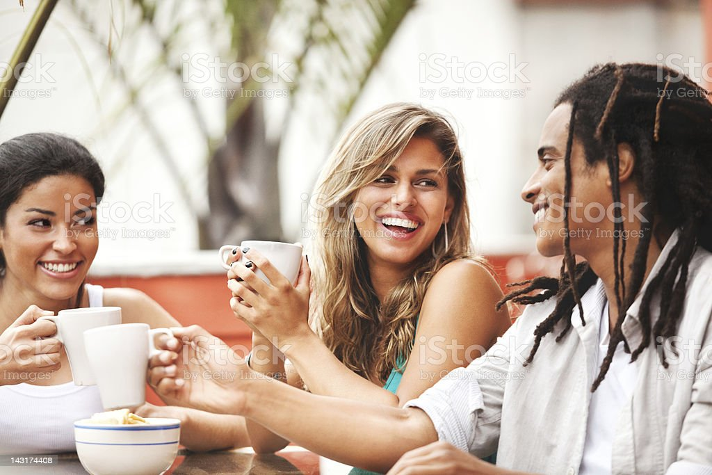 Three cheerful young friends enjoying each other's company in cafe. stock photo