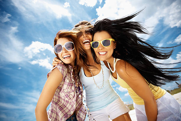 Three cheerful young friends wearing sunglasses against sky stock photo