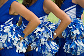 Three cheerleaders in blue and white uniform and pom-poms