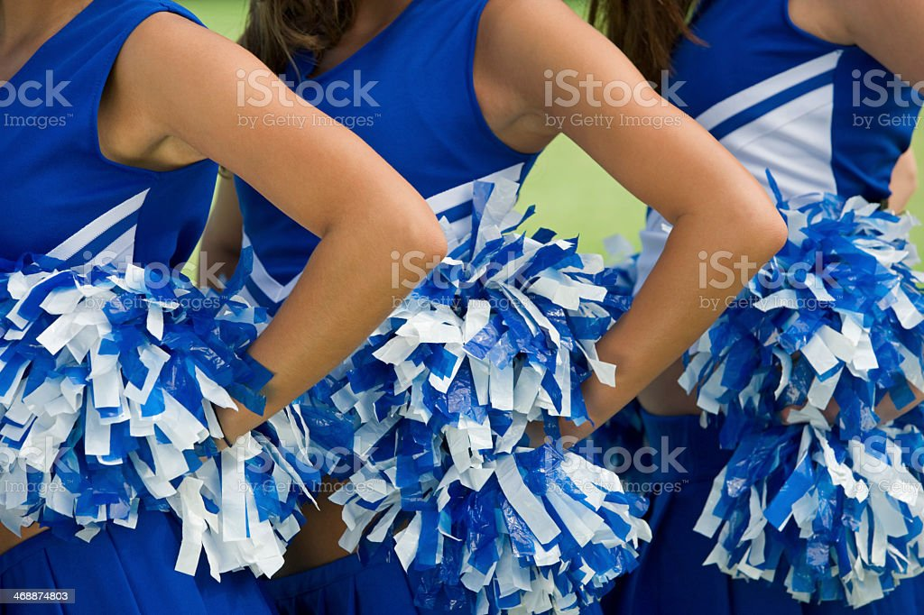 Three cheerleaders in blue and white uniform and pom-poms stock photo