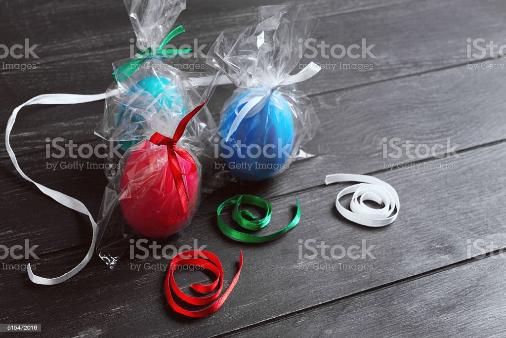 three chicken easter eggs in festive packaging with ribbons stock photo