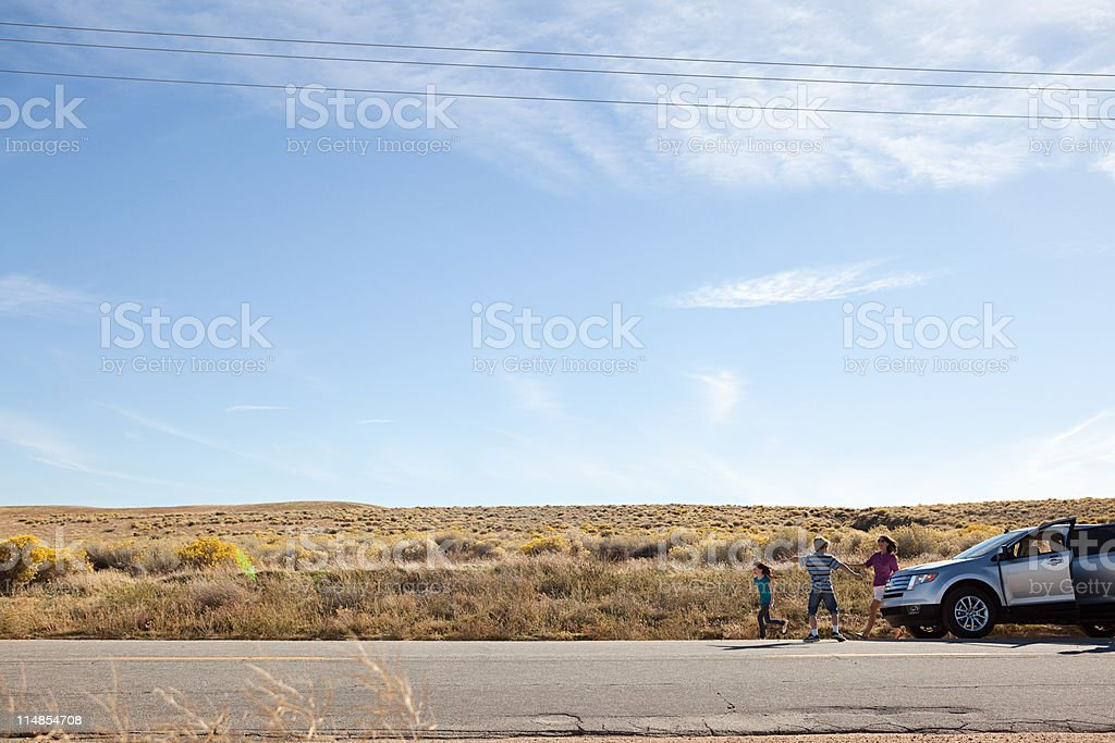 Three children by parked car in desert stock photo