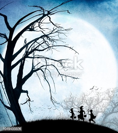 Three children dressed up for Halloween make their way across a grassy hill on their way to trick or treat are silhouetted against a large rising full moon.