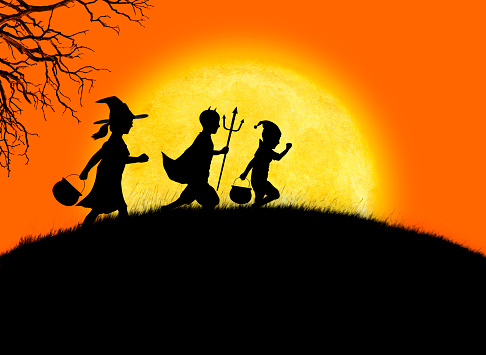 Three children dressed up for Halloween happily march up a small grass covered hill as they are silhouetted against a large full moon and orange sky.