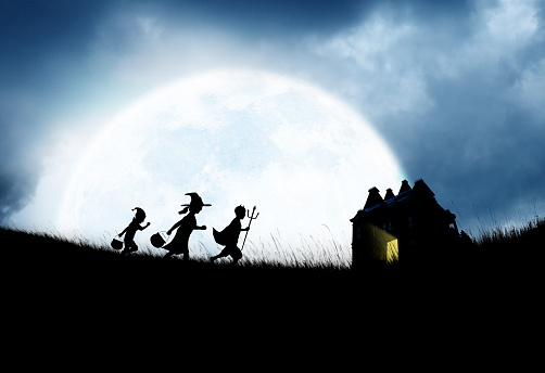 Three children dressed up for Halloween happily march down a small hill as they are silhouetted against a large full moon while on their way to trick or treating at a haunted house in the distance.