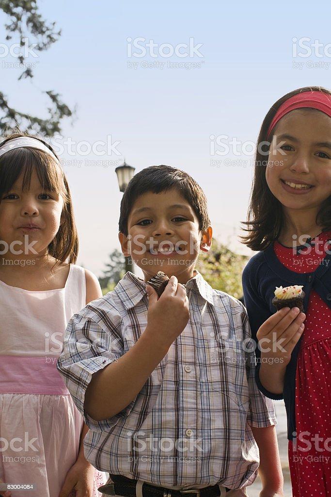 Three children eating cupcakes royaltyfri bildbanksbilder