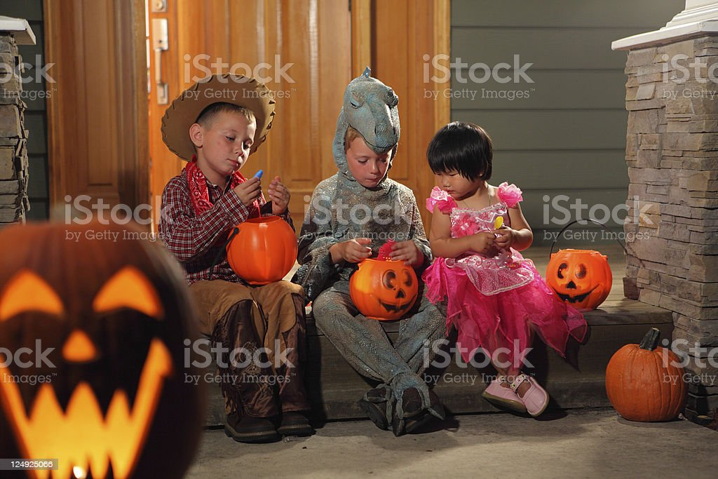 Three children eating their Halloween candy on the porch stock photo
