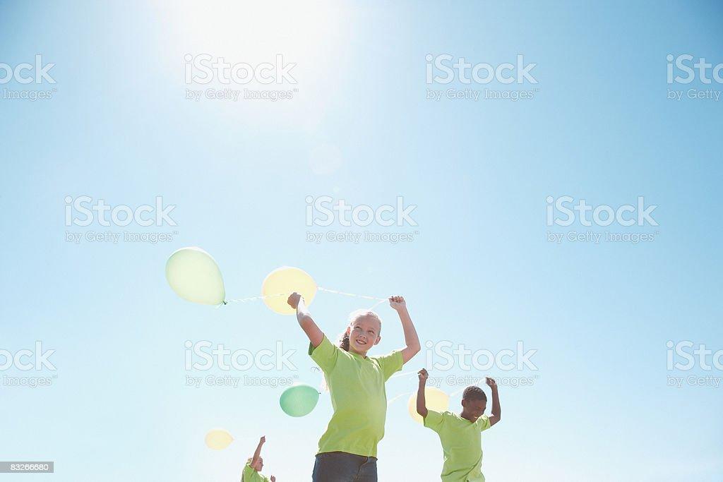 Troje dzieci Trzymając balony na zewnątrz zbiór zdjęć royalty-free