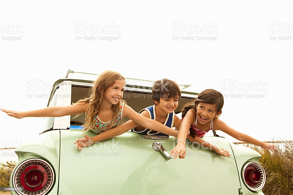 Three children in back of estate car with arms out stock photo