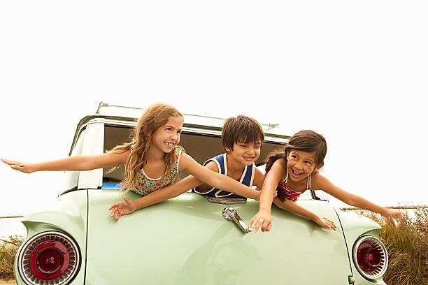 drei kinder auf dem rücken der estate auto mit ausgestreckten armen - kombi stock-fotos und bilder