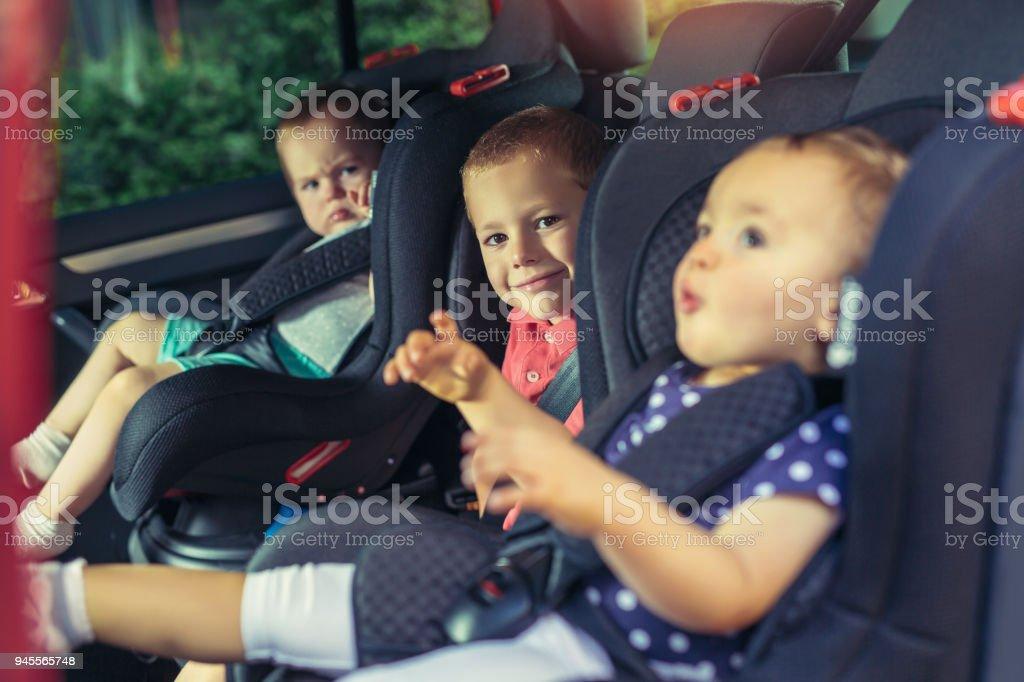 Tres niños en sillita de seguridad - foto de stock