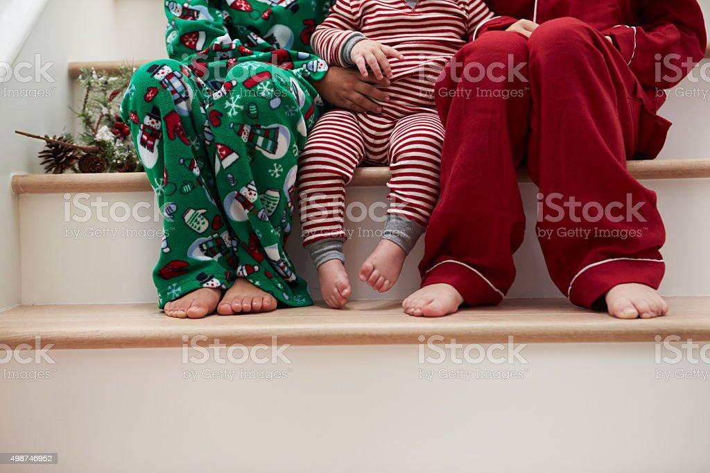 Tres niños en pijama sentado en las escaleras en Navidad - foto de stock