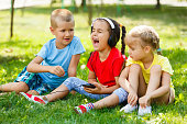 three children in the park are sitting on the grass with a phone