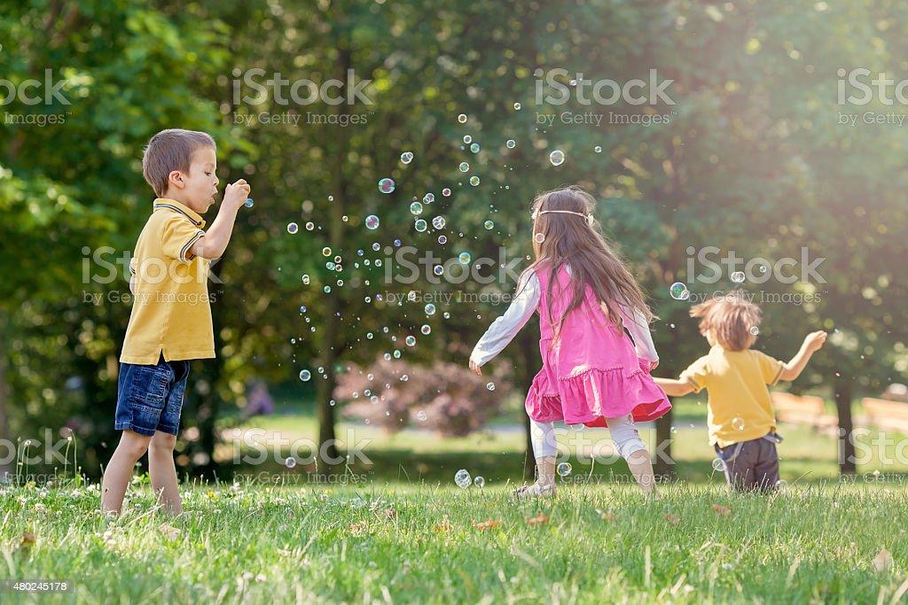 Tres niños en el parque soplando burbujas de jabón - foto de stock