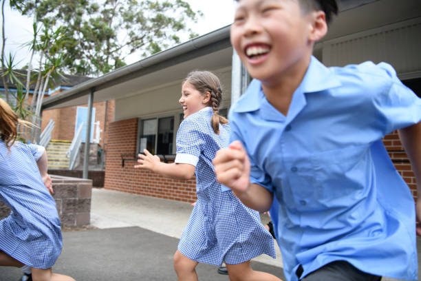 Three children laughing and running outside school stock photo