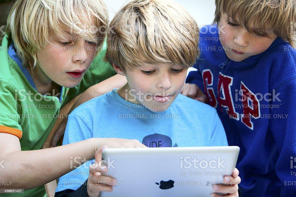three children looking at an iPad2 screen royalty-free stock photo