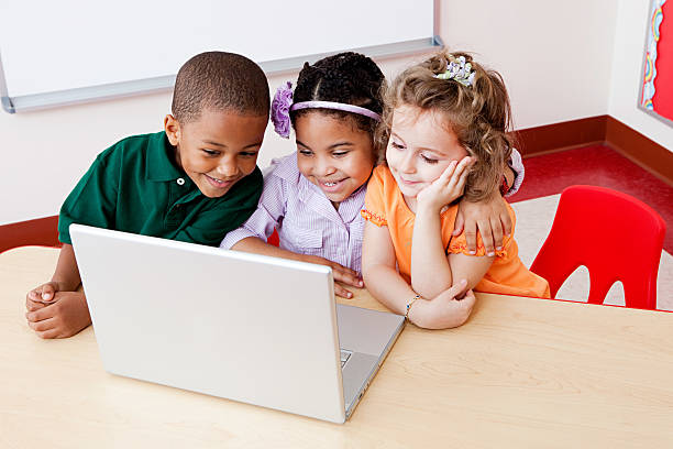Three children looking at the laptop together stock photo