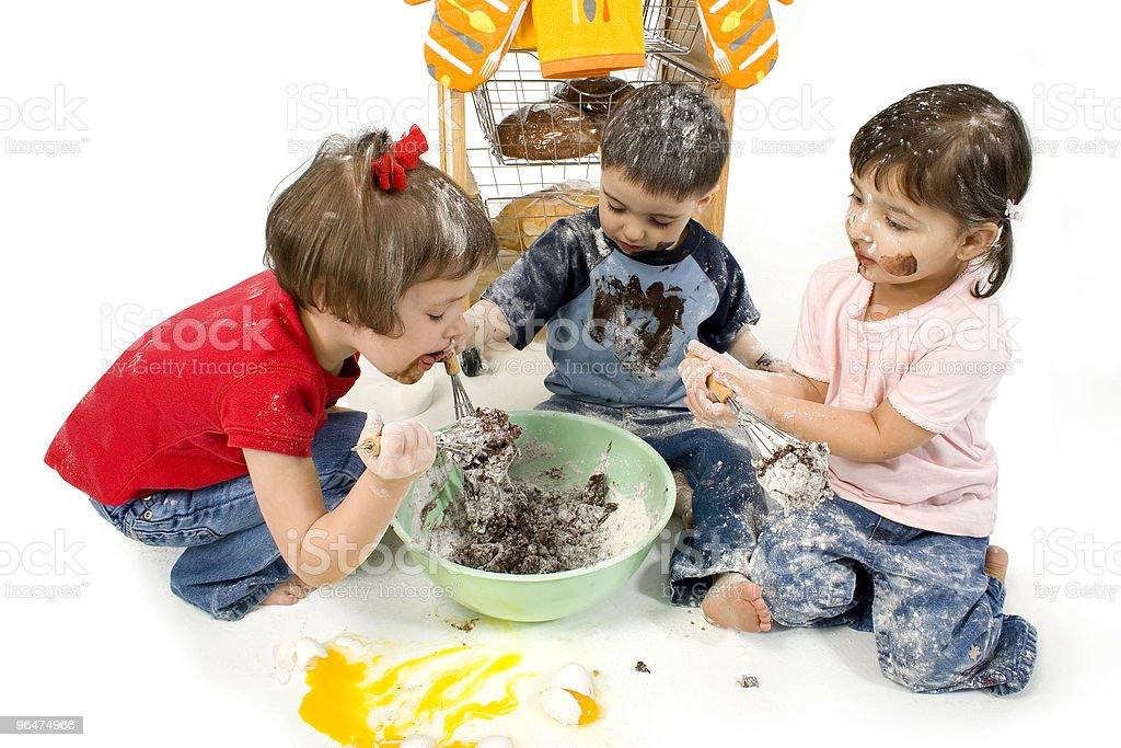 Three children making a mess while mixing baking ingredients royalty-free stock photo