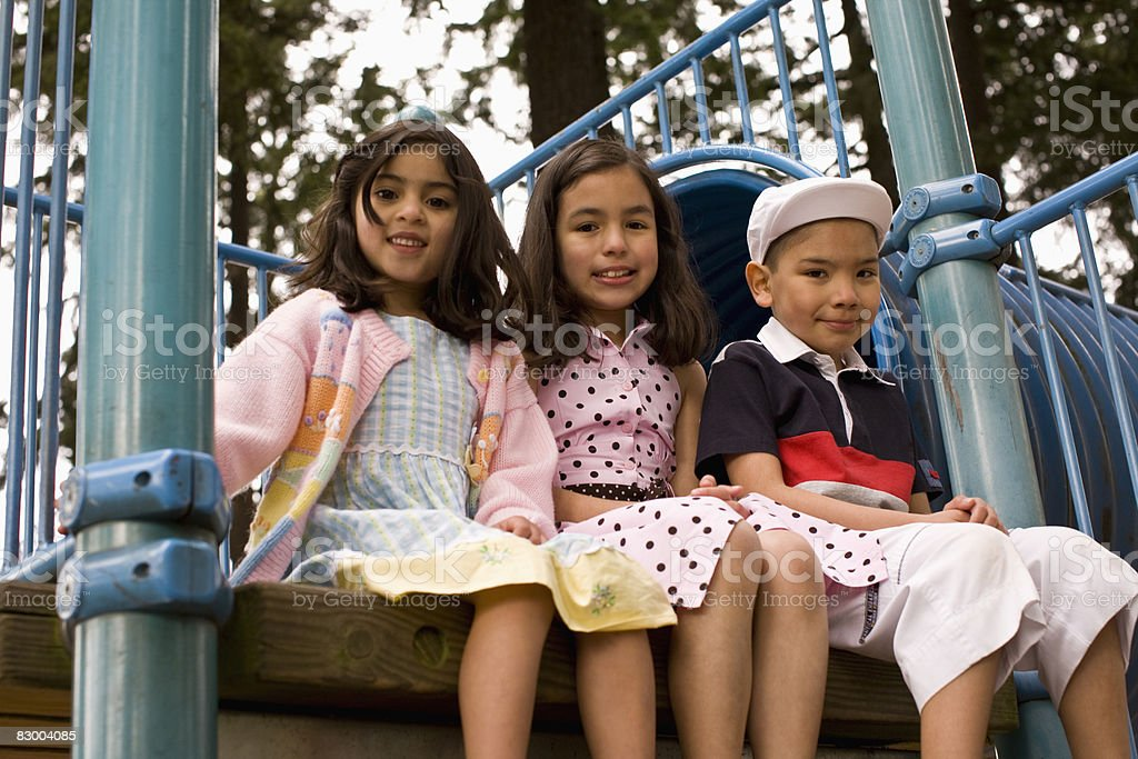 Three children on playground equipment royaltyfri bildbanksbilder