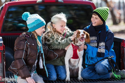 Three siblings with the family pet sitting in the back of a pickup truck.  The boy and two girls are dressed for cold weather, in jackets, hats and jeans.  The dog is the center of attention.  The children are 5, 9 and 11 years old.