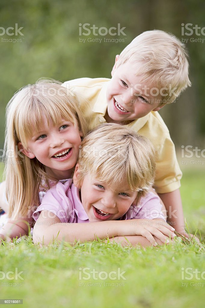 Three children playing outside royalty-free stock photo