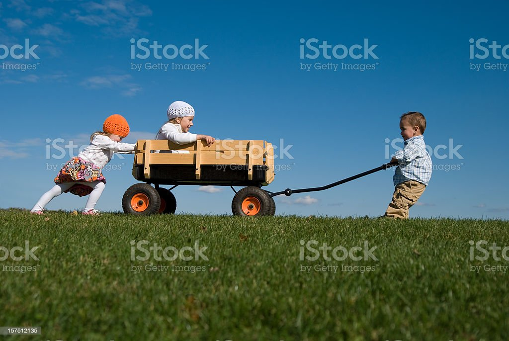 Three Children Pushing, Pulling, and Playing with Wagon royalty-free stock photo